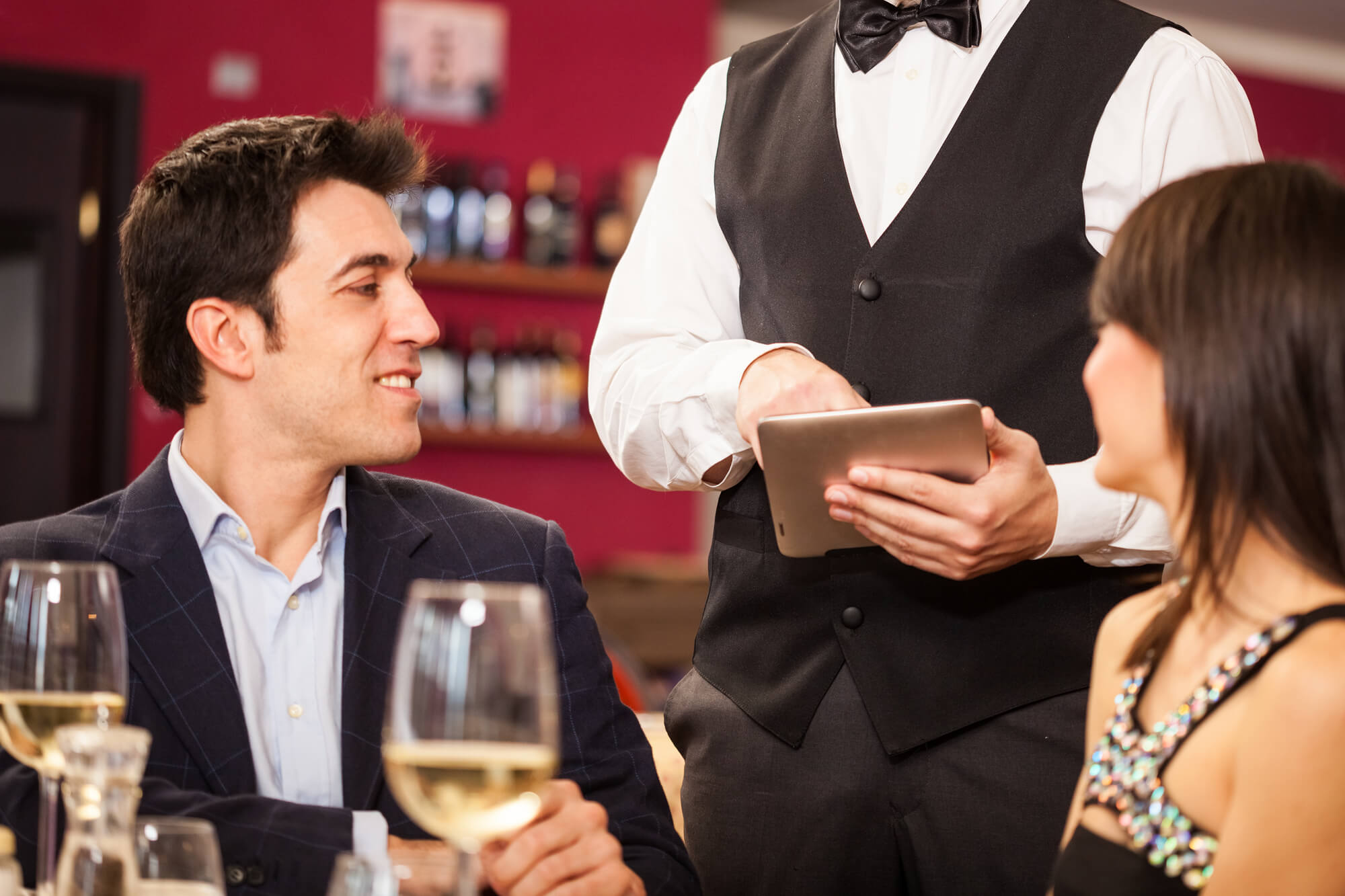 A couple eat dinner at a fancy restaurant, served by a waiter wearing a white shirt and a black vest. The man may be concerned about the effect of reducing fat on his testosterone levels.