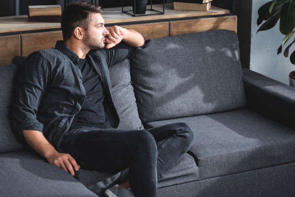A man in dark clothes sits on a gray sofa. He's gazing out the window, possibly worried about low testosterone and its effect on his sex drive.
