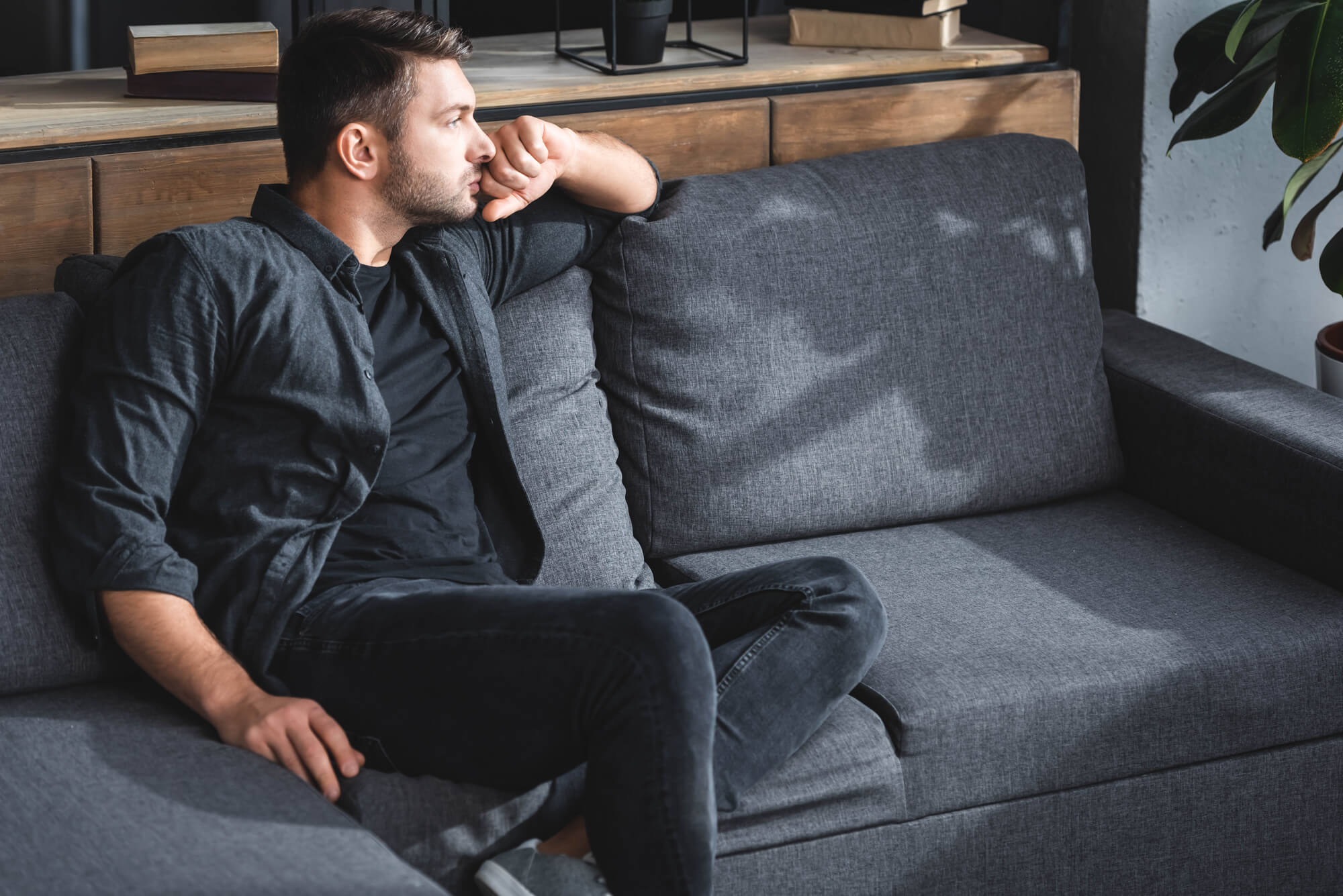 A man wearing a dark shirt and dark jeans sits on a gray sofa. He's staring out the window, possibly worrying about low testosterone and its effect on his sex drive.