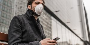 A man in a gray jacket wears a protective face mask as he uses his cellular phone. He may be researching the connection between low testosterone and Covid 19.