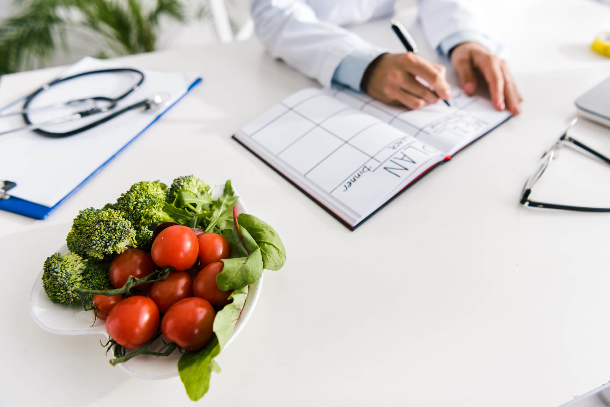 A dietician writes in a notebook near a bowl of vegetables. Scientists are studying the connection between low testosterone and inflammatory foods.