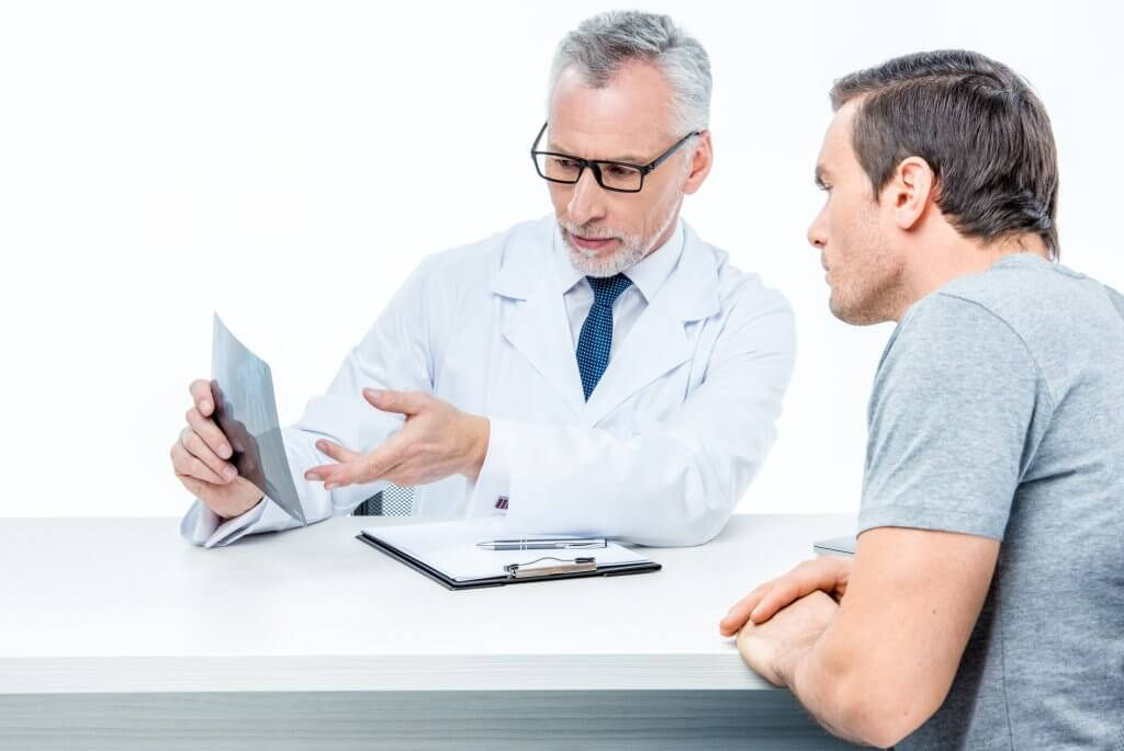 A male doctor wearing glasses is sitting at a white table with his male patient. The doctor is showing him a scan and explaining something, possibly how testosterone can affect prostate cancer.