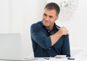 A middle-aged man in a dark blue shirt sits in front of his computer, massaging his shoulder and grimacing in pain. It's important that people in pain understand the connection between opioids and chronic low testosterone.